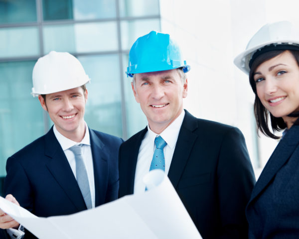 Three construction engineers holding a blueprint outdoors as they look at you